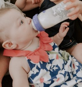 toddler feeding baby a bottle of milk