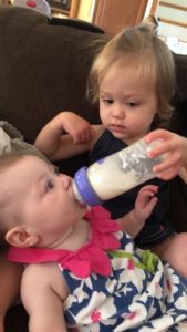 toddler feeding baby