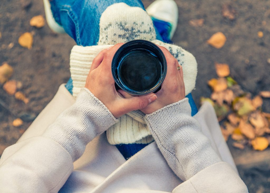 woman holding a coffee cup outside with fall leaves practicing self care
