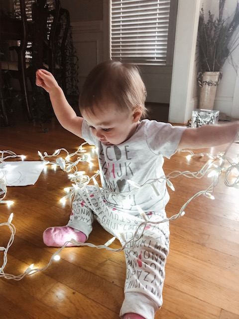 toddler playing with Christmas lights
